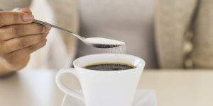 USA, New Jersey, Jersey City, Close-up of woman sweetening coffee